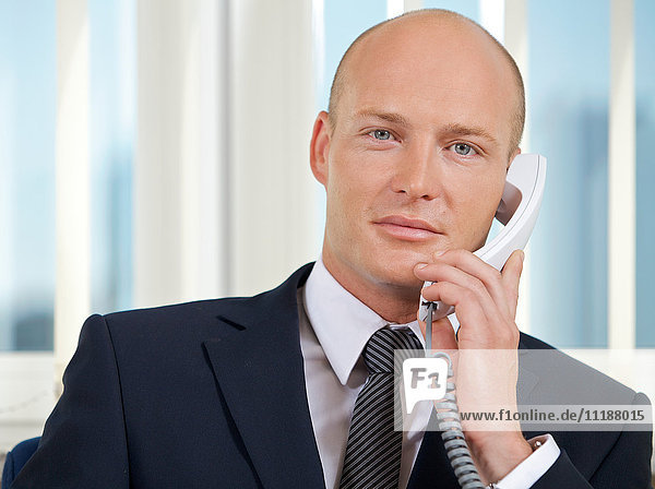Portrait of businessman talking on telephone at office