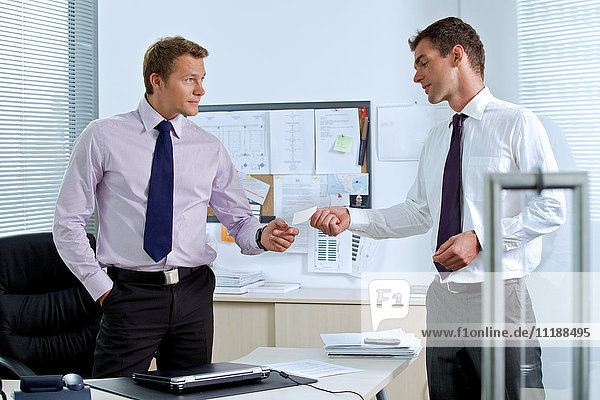 Businessman giving visiting card to colleague