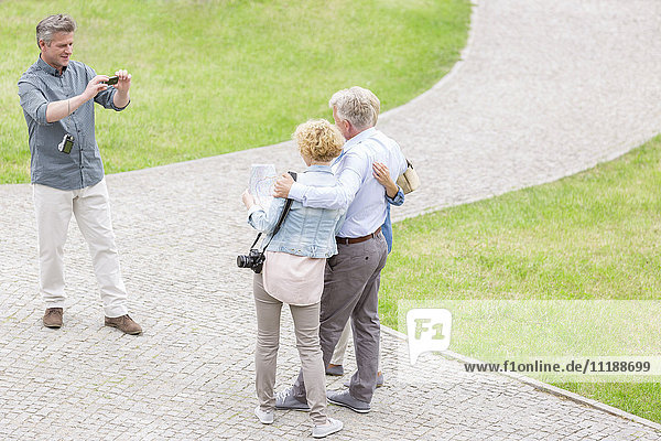 High angle view of man photographing friends at park