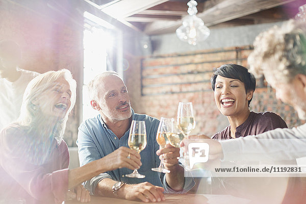 Friends toasting white wine glasses at restaurant table