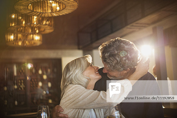 Senior couple hugging and kissing in bar