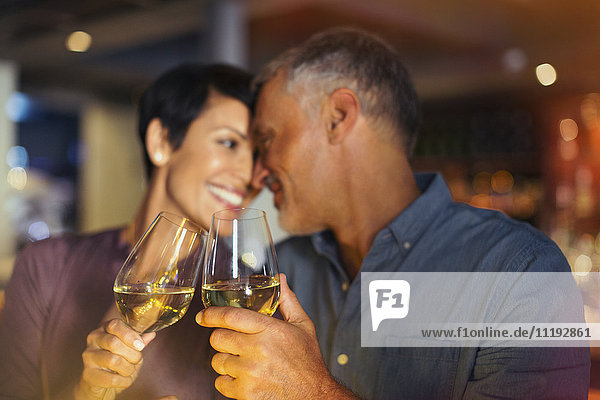 Affectionate couple toasting white wine glasses in bar