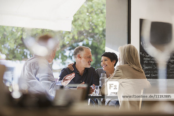 Affectionate couple dining with friends at restaurant table