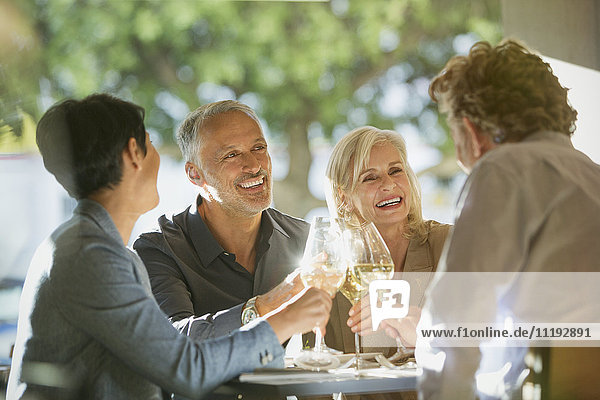 Couples toasting white wine glasses at sunny restaurant table