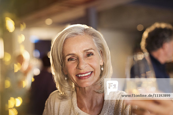 Portrait smiling senior woman toasting white wine glass at bar
