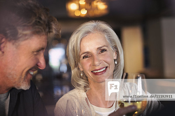 Portrait smiling senior couple drinking white wine in bar