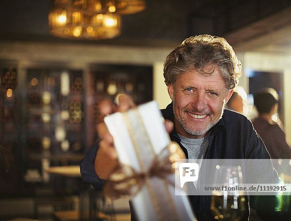 Portrait smiling senior man giving gift in bar