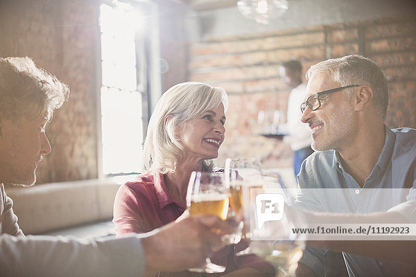 Smiling friends toasting beer and wine glasses in restaurant