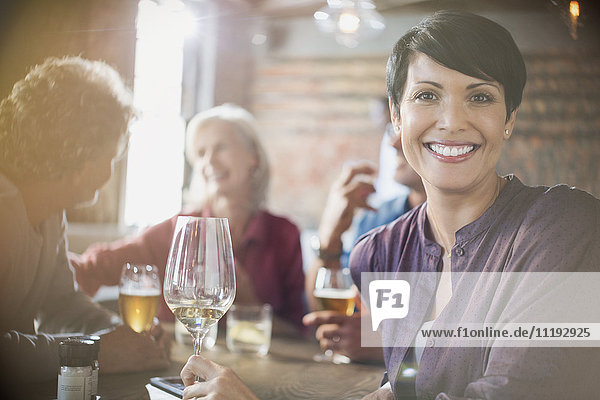 Portrait smiling woman drinking white wine dining with friends at restaurant table