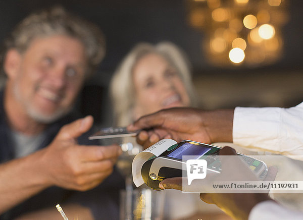 Close up waiter using credit card machine returning credit card to couple
