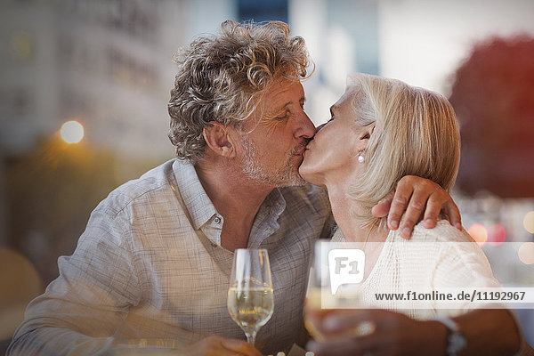 Affectionate senior couple kissing drinking white wine at sidewalk cafe