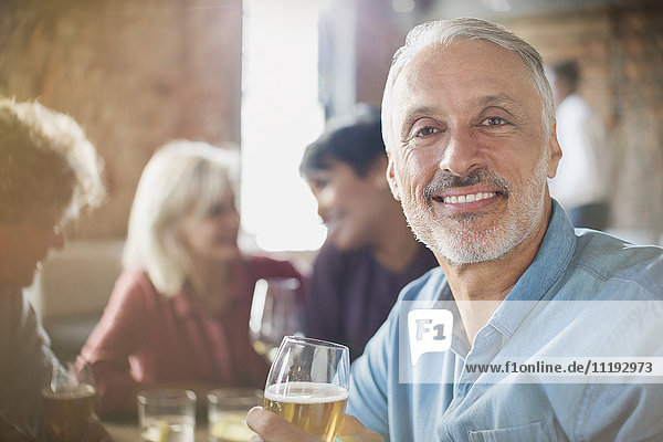 Portrait confident man drinking white wine with friends at restaurant table