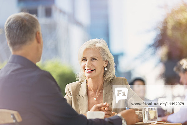 Smiling businesswoman listening to businessman at sunny urban sidewalk cafe