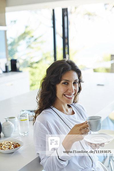 Portrait smiling woman in bathrobe drinking coffee in morning kitchen