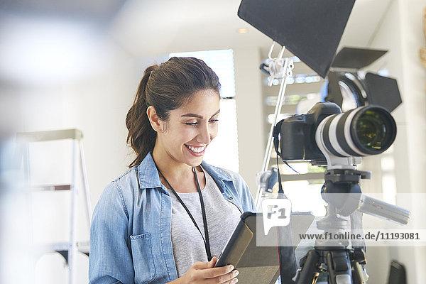 Female photographer using digital tablet behind camera in studio