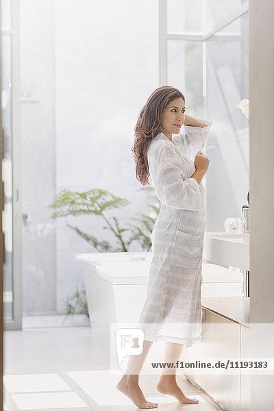 Brunette woman in bathrobe at bathroom mirror