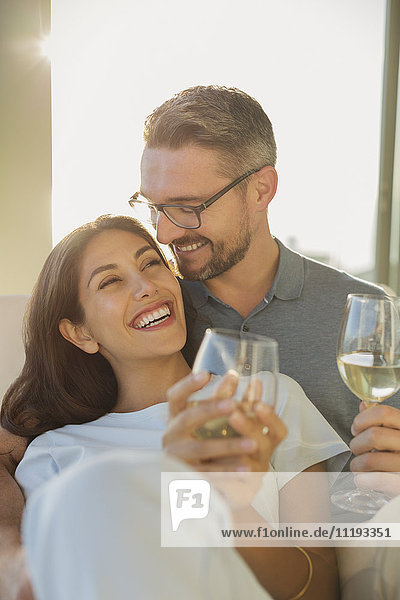 Affectionate couple smiling and drinking white wine