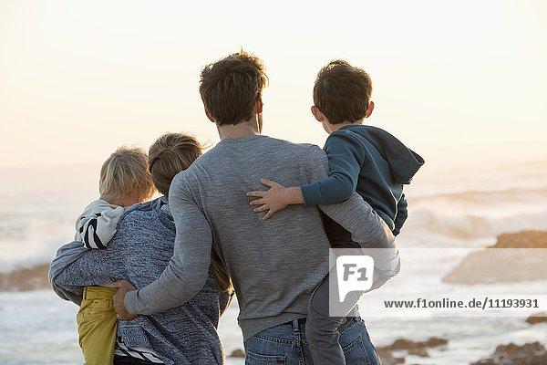 Glückliche junge Familie mit Blick auf das Meer am Strand bei Sonnenuntergang
