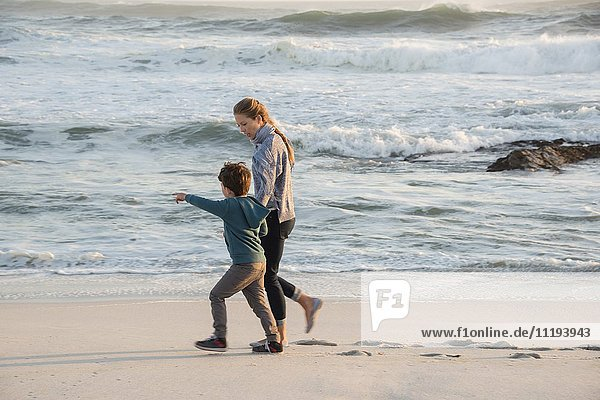 Glückliche Mutter und Sohn  die am Strand spazieren gehen.