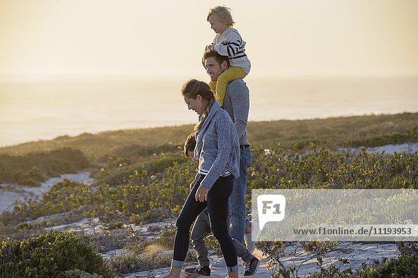 Glückliche junge Familie  die bei Sonnenuntergang am Strand spazieren geht.
