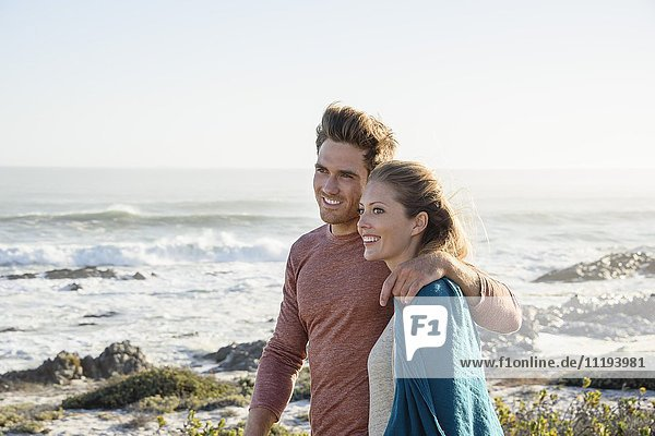 Glückliches Paar  das am Strand spazieren geht