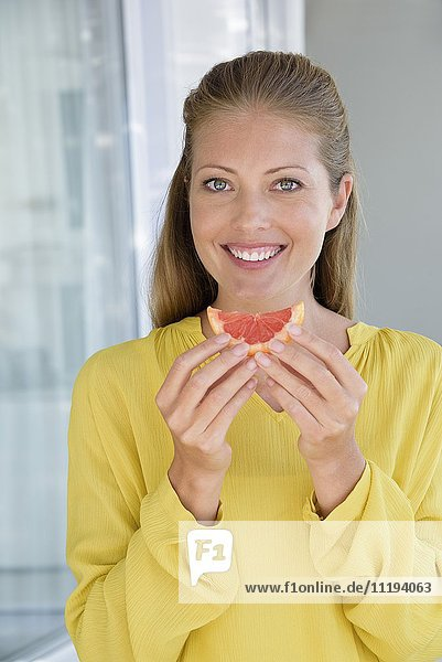 Close-up of a happy beautiful woman eating grapefruit