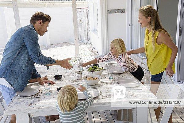 Junge Familie genießt Essen auf der Veranda