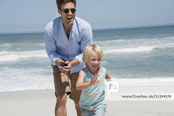 Junger Mann spielt mit seinem Sohn am Strand.