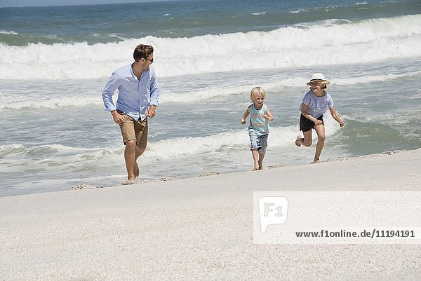 Young man running on the beach with his children