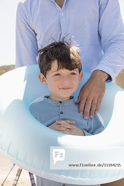 Happy father and son with rubber ring on beach