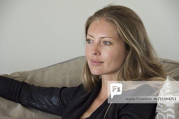 Glückliche schöne Frau auf dem Sofa sitzend