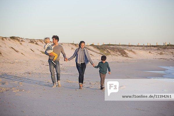 Familienspaziergang am Strand mit gegenseitiger Händehaltung