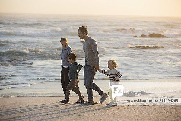 Profil einer Familie  die am Strand spazieren geht