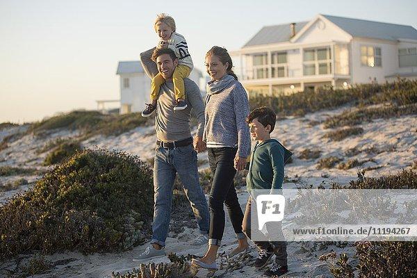 Paar mit ihren beiden Kindern  die am Strand spazieren gehen.