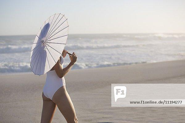 Frau mit Sonnenschirm am Strand