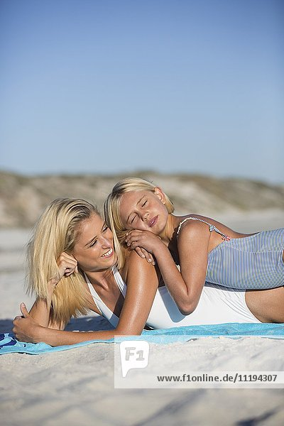 Pretty mother and her daughter lying on the beach