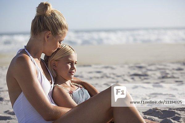 Glückliche Frau und ihre Tochter am Strand sitzend