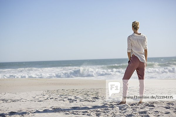 Schöne junge Frau am sonnigen Strand stehend