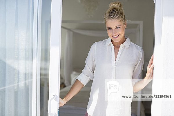 Portrait of happy young woman standing by window