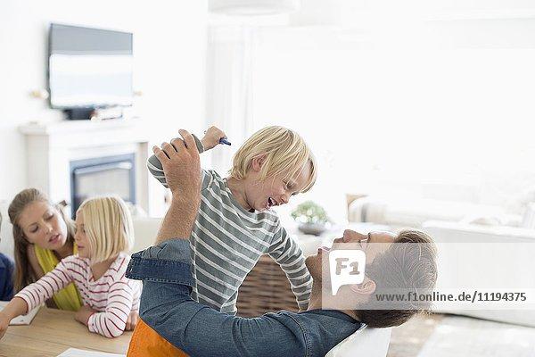 Junger Mann spielt mit seinem Sohn zu Hause