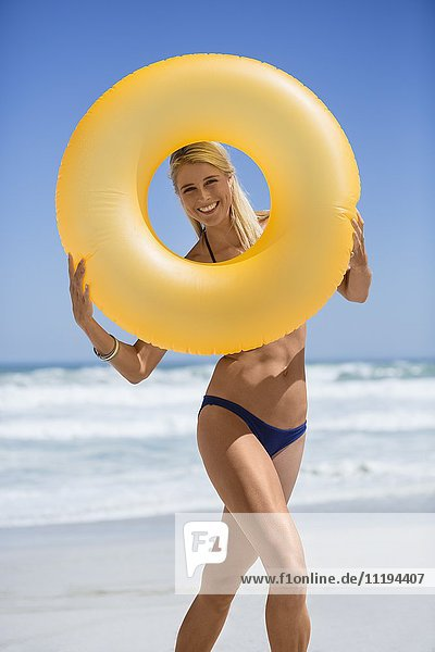 Happy woman peeking from hole of inflatable ring