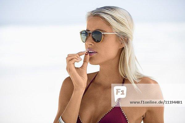Close-up of a young beautiful woman eating beta-carotene capsule