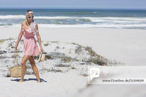 Schöne junge Frau  die am Strand spazieren geht.