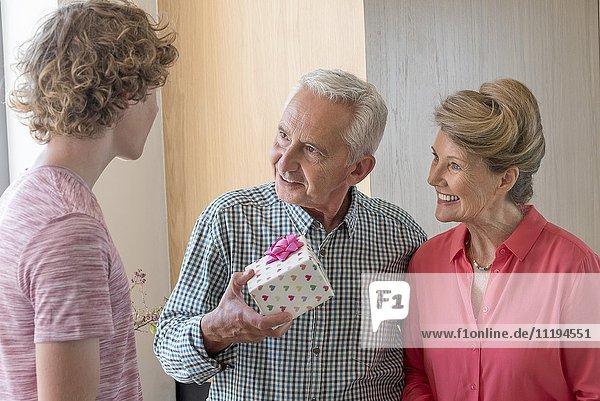 Glückliche Großeltern und Teenager-Enkel mit Geburtstagsgeschenk zu Hause
