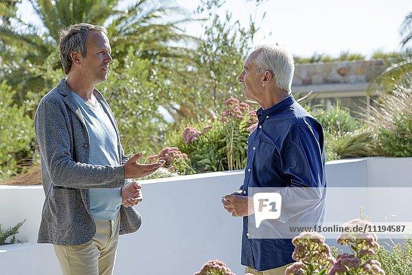 Reifer Mann im Gespräch mit seinem älteren Vater im Garten