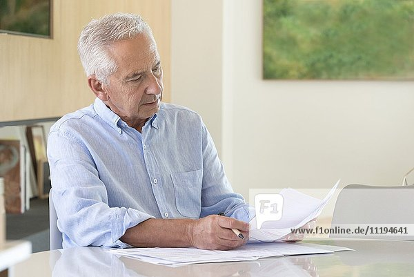 Senior man doing paperwork at home