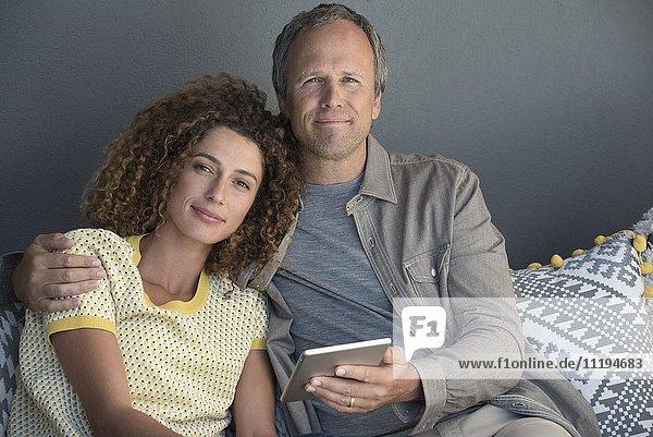 Porträt eines Paares  das auf einer Couch mit einem digitalen Tablett sitzt.