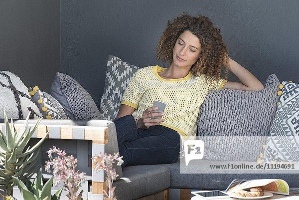Frau sitzt auf einer Couch und benutzt ein Smartphone.