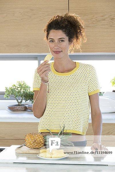 Porträt einer jungen Frau beim Essen einer Ananasscheibe