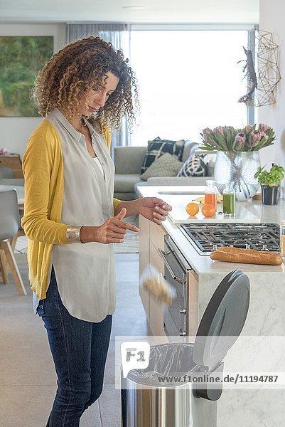 Frau wirft Beutel mit Essen in den Mülleimer